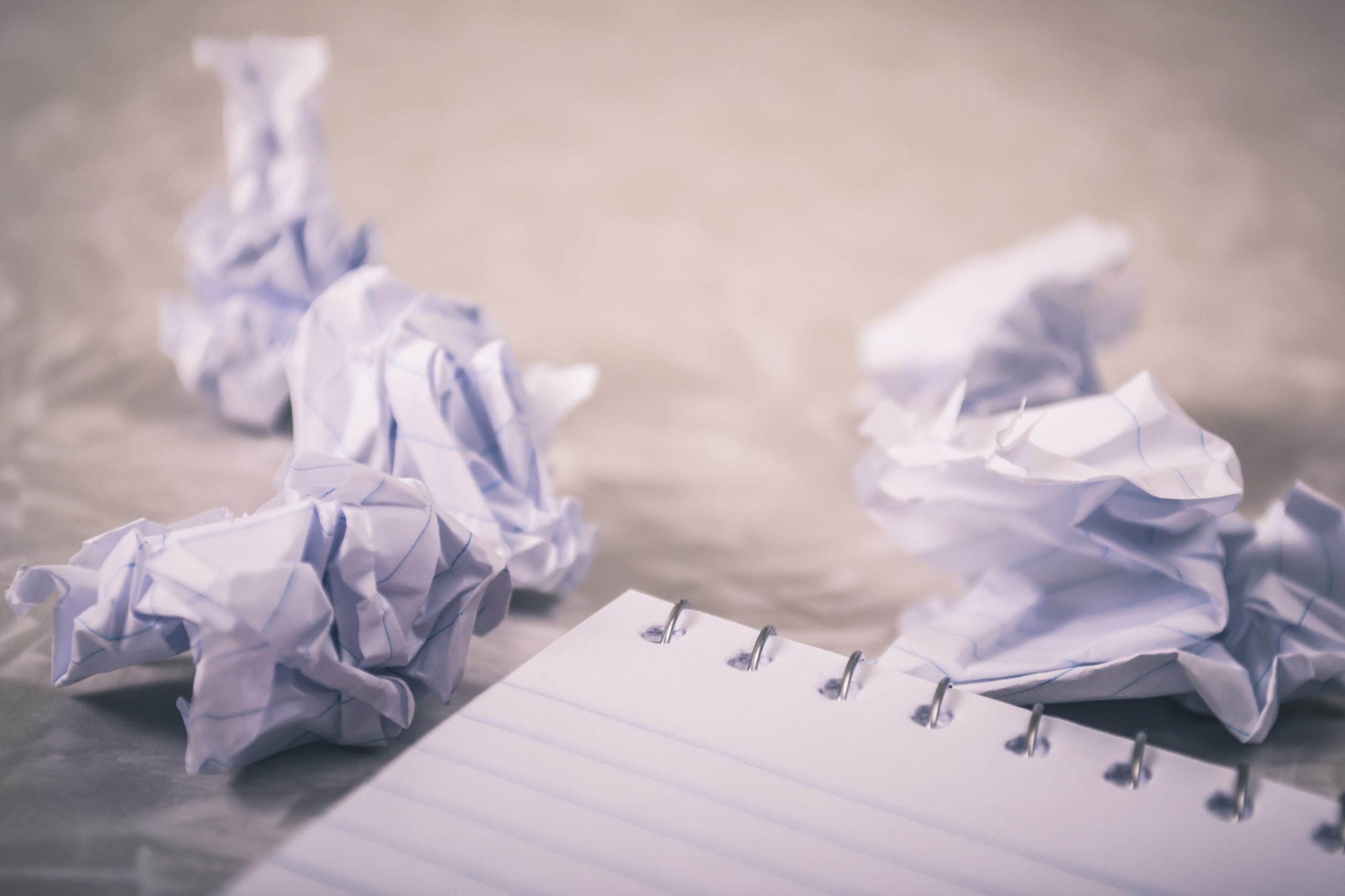 photo of screwed up paper and blank notepad for post five creative steps for overcoming writers block