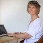 gail sitting at laptop for post trends in writing for 2021