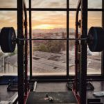 photo of weights on frame overlooking city sunset scene for blog working your writing muscles