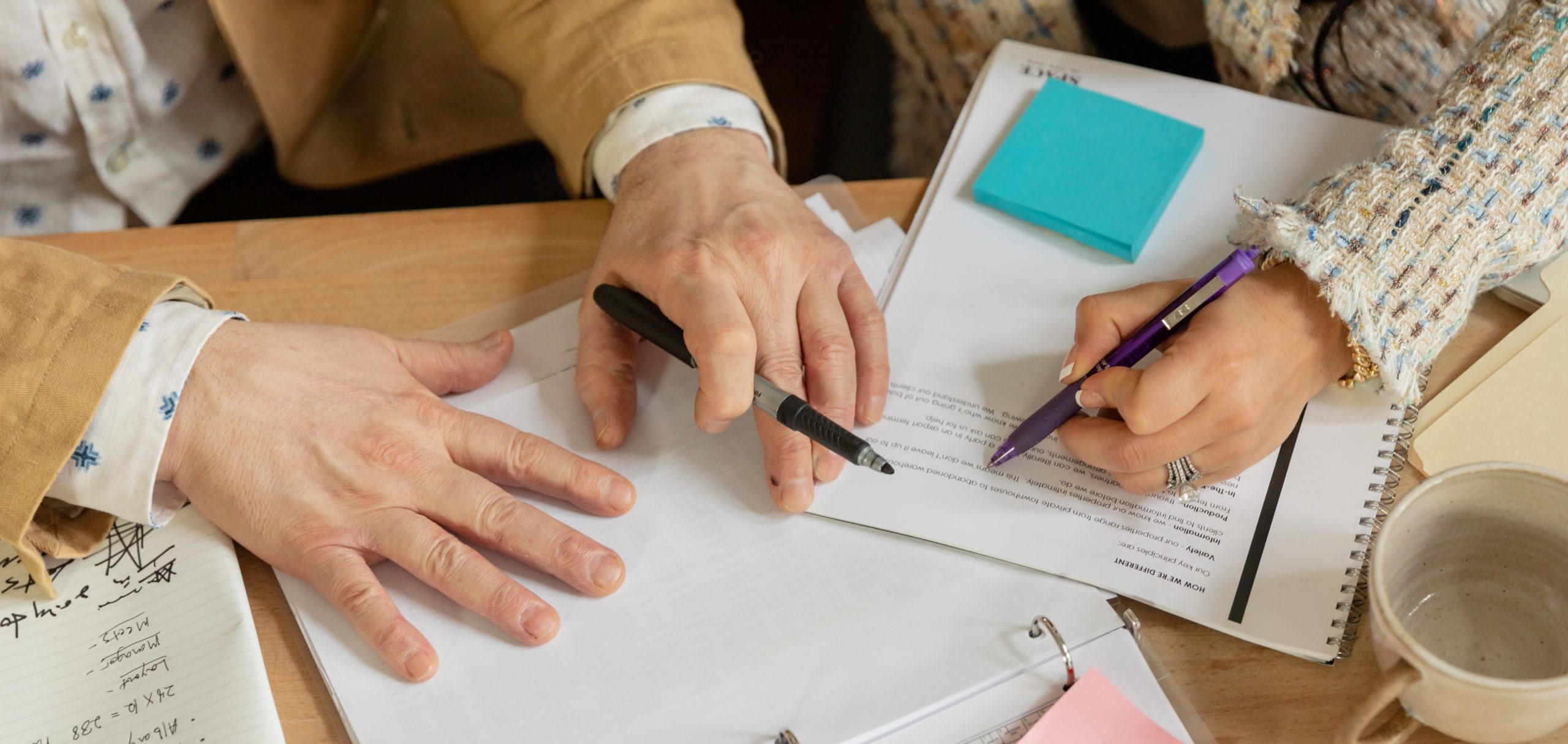 Two people's hands with pen and paper for blog common grammar mistakes I